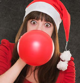 Woman blowing balloon and wearing a christmas hat — Stock Photo