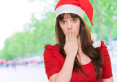 Woman wearing a christmas hat and covering her mouth — Stock Photo