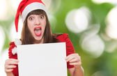 Surprised christmas woman holding a blank card — Stock Photo