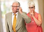 Muž na mobil před žena ukázal — Stock fotografie