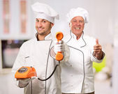 Young Chef Holding Telephone In Front Of Mature Chef — Стоковое фото