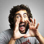 Portrait of young man screaming against a grey background — Stock Photo