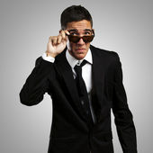 Portrait of business man taking off the sunglasses against a gre — Stock Photo
