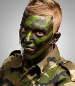 Portrait of a soldier with camouflage painting — Stock Photo