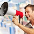 Portrait Of A Handsome Young Man Shouting With Megaphone — Stock Photo #18770903