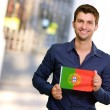 Young Man Holding Portuguese Flag - Stock Photo