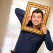 Young Man Holding Picture Frame - Stock Photo