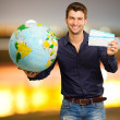 Young Man Holding Globe And Boarding Pass — Stock Photo #18778857