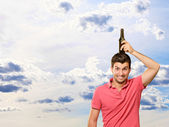 Portrait Of Young Man Holding Bottle On Head — Stock Photo