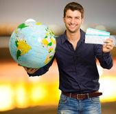Junger mann hält globus und boarding pass — Stockfoto