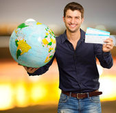 Ung man håller världen och boarding pass — Stockfoto