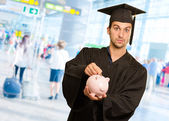 Graduate Man Inserting Coin In Piggybank — Stock Photo