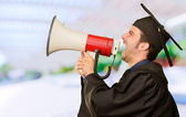 Graduate Man Shouting Into The Megaphone — Stock Photo