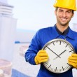 Happy Engineer Holding Wall Clock — Stock Photo