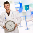 Happy Male Doctor Holding Clock — Stockfoto