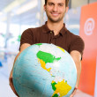 Young Man Holding Globe - Stock Photo