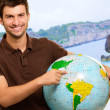 Young Man Showing Destination On Globe - Stock Photo