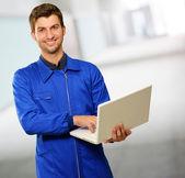 Feliz jovem técnico trabalhando no laptop — Foto Stock