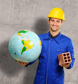 Happy Young Construction Worker Holding Globe And Brick — Fotografia Stock