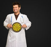 Scared Young Doctor Holding Bulls Eye — Stock Photo