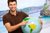Young Man Showing Destination On Globe — Stock Photo