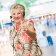 Senior Woman With Headset Showing Thumb-up Sign — Stock Photo