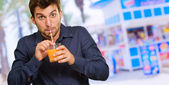 Young Man Sipping Juice Through Straw — Stock Photo