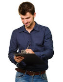 Young Man Writing On Clipboard — Stock Photo