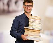 Glad ung håller hög med böcker — Stockfoto