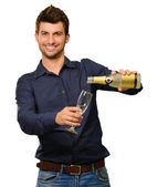 Happy Young Man Pouring Champagne Into Glass — Stock Photo