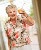 Mulher madura, segurando o copo de suco — Foto Stock