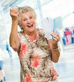 Senior mujer sosteniendo en miniatura y embarque — Foto de Stock