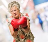 Zły starsza kobieta sobie rękawice bokserskie — Zdjęcie stockowe