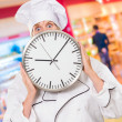 Worried chef hiding behind a clock - Stock Photo