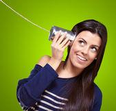 Mujer sosteniendo una lata de metal como un teléfono — Foto de Stock