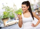 Jovem mulher segurando e comendo uma maçã — Foto Stock