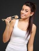Young girl Holding Sushi Roll with chopsticks — Stock Photo