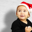 Stock Photo: Baby boy wearing a christmas hat and looking up