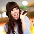 Girl With Headset Singing On Mike — Stock Photo #18817769