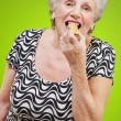 Portrait of a woman eating granola bar — Stock Photo #18818329