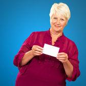 Senior Woman Holding A Card — Stock Photo
