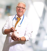 Male Doctor Putting Coins In A Piggy Bank — Stock Photo