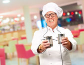 Senior Chef Holding Tin Cans — Stock Photo