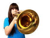 Portrait of a young girl blowing trumpet — Stock Photo