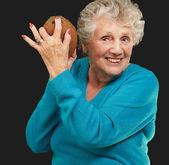Senior happy woman holding coconut — Stock Photo
