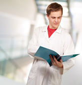 Portrait of a young doctor reading a folder — Stock Photo
