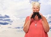 A Senior Woman Holding Binoculars — Stock Photo