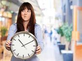 Una joven sosteniendo un reloj y poniendo cara de — Foto de Stock
