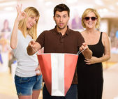Man Holding Shopping Bag In Front Of Two Happy Women — Stock Photo