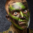 Closeup of angry soldier with painting - Stock Photo